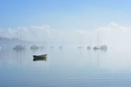 Lonely dinghy anchored on flat calm water with boats moored in background in morning fog.