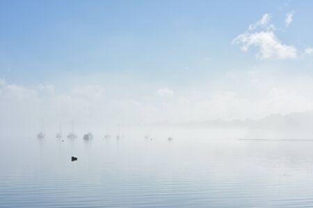 Lonely buoy on flat calm water marking anchorage with boats moored in background in morning fog.