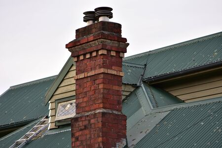 Vintage brick chimney on old house with corrugated iron roof. Imagens