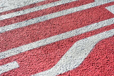 Detail of red and white pattern on coarse concrete surface.