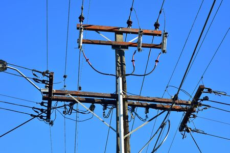 Power grid intersection on concrete pole with isolators and wires coming from four sides.