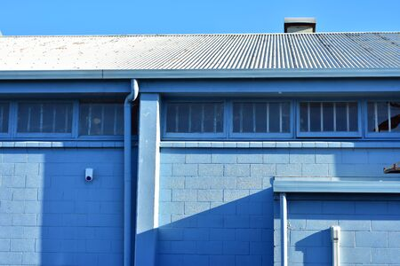 Back side of industrial building painted pale blue with windows with metal bars and corrugated metal roof.