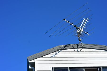 Multi channel aerial above roof of wooden house with clear blue sky in background.