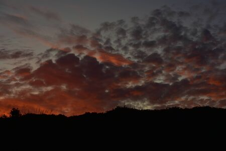 Late evening sky with dark orange to violet clouds after sunset. Imagens