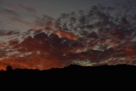 Late evening sky with dark orange to violet clouds after sunset. Zdjęcie Seryjne