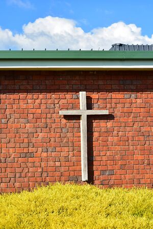 Wooden Christian cross on red brick exterior wall of contemporary church building.