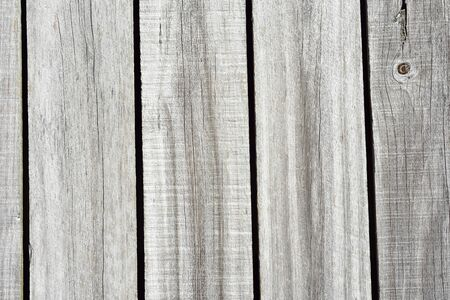 Detail of sun bleached wooden fence with vertical slates.