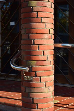 Round pillar made of red bricks with stainless steel tube railing curved around it.