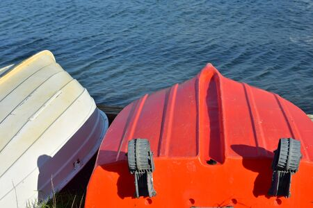 Two small plastic dinghies bottom up on shore with calm water surface in background.