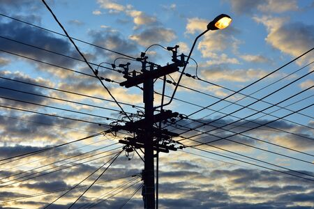Power grid intersection silhouette with bright street light and sunset sky in background.