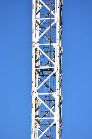 Detail of steel structure of tower crane painted white with ladder through center. Zdjęcie Seryjne