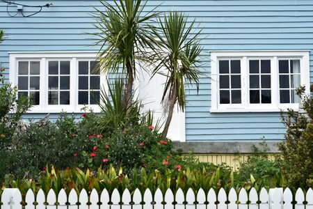 Old wooden house with pale blue exterior paint and flower garden behind white slate fence. 版權商用圖片