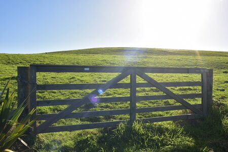 Heavy wooden livestock gate separating sections of farmland in back light.