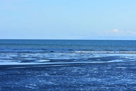 Shallow ocean coast with thin layer of water on sandy surface forming pattern with a lot of contrasts.