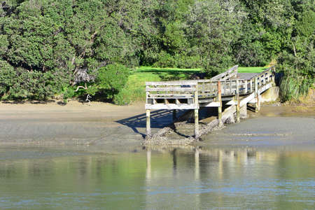 Small wooden jetty with legs covered with oyster shells on shore of calm estuary at low tide. 版權商用圖片