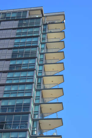 Detail of tall mostly steel and glass building with corner balconies protruding far off facade.