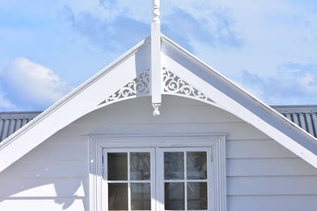 Roof top of classic white wooden villa with multi pane window and carved finial. 版權商用圖片