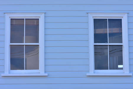 Vintage windows with four glass panes on wooden pale blue wall with weatherboard cladding.