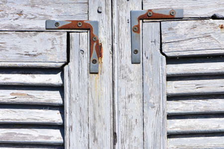 Weathered wooden window shutters with white paint peeling off and rusty strengthening metal pieces.
