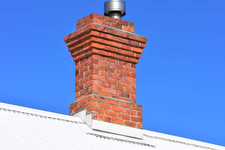Vintage red brick chimney with modern metal lining on top of white corrugated sheet metal roof. 免版税图像