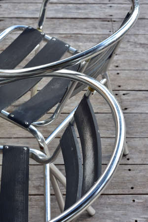Outdoor chairs made of chromed tube frames with weathered alloy seats and back rests on wooden veranda. 版權商用圖片