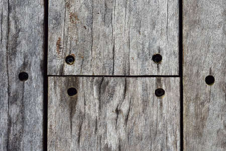 Detail of weathered wooden veranda floor with planks screwed into frame.
