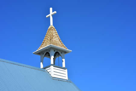 White cross on top of tiny wooden belfry of small village church.