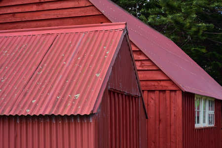 Detail view of red painted vintage sheds made from corrugated sheet metal and wood slates. 版權商用圖片