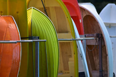 Colourful dinghies of various sizes and materials standing in row in metal tube rack. 版權商用圖片