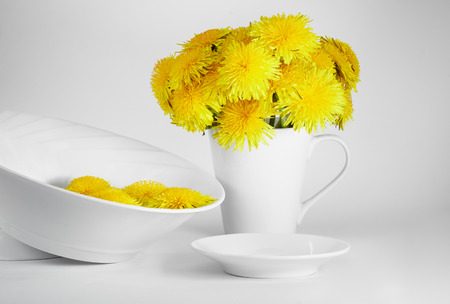 Composition of bouquet of dandelions, blank small plate and a bowl filled with water and dandelions' buds over it