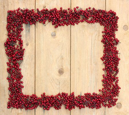 Autumn frame from red berries of haw thorn tree flat on rough wooden background, flatlay composition, closeup, copy space for your design