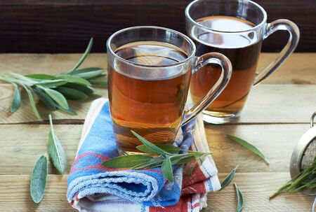 Sage herbal tea or decoction in  two glass cups with herb leaves all around on linen blue with red napkin and wooden table, closeup, copy space, alternative medicine and naturopathy concept