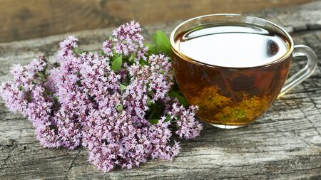 Wild origanum flower tea or decoction, marjoram buds on old textured rustic wooden background, closeup, copy space, alternative medicine and naturopathy concept