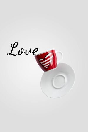 Love writing spilled out of valentine's cup of coffee with heart balancing in the air or falling isolated on white background, levitation creative design, St Valentine's, mothers or womens day concept, closeup Standard-Bild