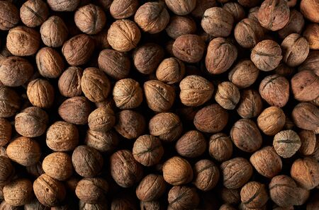 Walnut heap textured background for your design, closeup, from above top view, eco organic food and vegegtarian eating concept