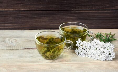 Yarrow herbal healing tea or decoction with fresh milfoil flowers nearby on rustic wooden table, closeup, copy space, alternative medicinal and naturopathy concept