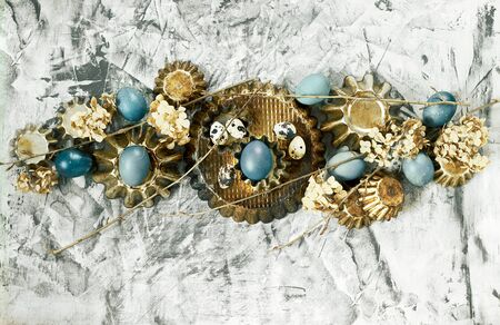 Easter composition from blue eggs, cake forms, tree branches, dry flowers on concrete background, copy space, Christian religious festival concept and design