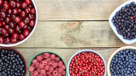 Bowls with fresh garden and forest berries: raspberry, sweet cherries, red and black currant, blueberry, purple shadberry overhead on the wooden table, flat lay, from above top viiew, closeup, copy empty space for your design Standard-Bild