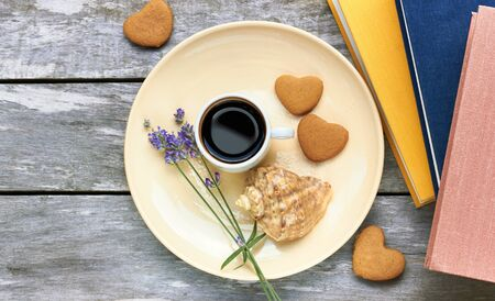 Scandinavian vacation breakfast at the sea: coffee, heart shaped cookies, lavender, shell and books on old weathered wooden table, enjoy simple moments of your life concept, flat lay, from above top view, copy space