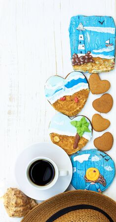 Coffee, beach hat, shell and heart shaped cookies with painted gingerbread of sea, beach, beacon and a girl on white wooden table, vertical, closeup, copy space, vacation and holiday leisure time concept