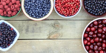 Many bowls with fresh garden and forest berries: raspberry, blueberry, red and black currant, sweet cherries overhead on the wooden table, flat lay, from above top viiew, closeup, a frame with empty space for your design Standard-Bild