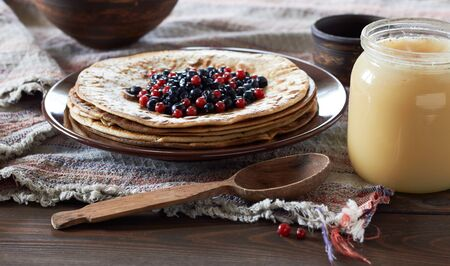 Pancake week hot cakes with berries, honey and butter on rustic background, closeup, copy space, shrovetide and homemade food concept