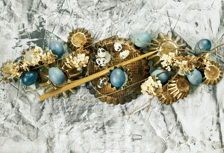 Easter composition from blue eggs, cake forms, tree branches, dry flowers and candles on concrete background, copy space, Christian religious festival concept and design