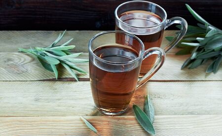 Sage herbal tea or decoction in a glass cups with herb leaves all around on wooden table, closeup, copy space, herbal drinks for winter concept