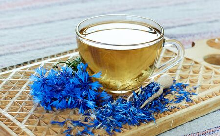 Blue cornflower or centaurea flower tea is good as diuretic, in cosmetics and eyewash, fresh blossom and a jar with dry petals nearby, closeup, copy space, herbal drinks concept