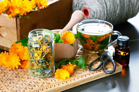 Calendula herb, a jar with dry marigold, a mortar with fresh bunch of flowers, a cup of herbal tea, a bottle of medicinal healing tincture and other stuff on wooden board,  closeup, copy space, alternative medicine concept