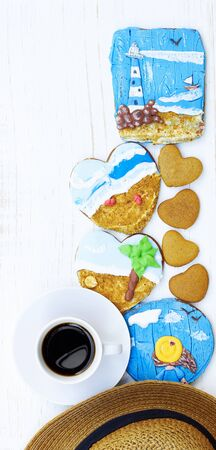 Coffee, beach hat and heart shaped cookies with painted gingerbread of sea, beach, beacon and a girl on white wooden table, vertical, closeup, copy space, vacation and holiday leisure time concept