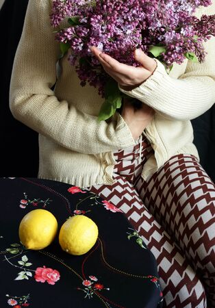 Woman holding a bouquet of blooming lilac sitting at the table with lemons on it, body part crop, closeup, copy space, vertical
