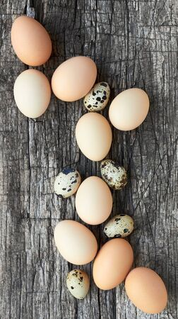 Egg composition on textured wood background, copy space, closeup, vertical, flat lay, from above top view, easter concept and design