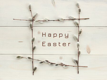 Happy easter in spring frame from pussy-willow branches flat on white wood, minimalism monochrome composition, empty space for your design, closeup, palm sunday, easter and mothers day holidays concept Standard-Bild